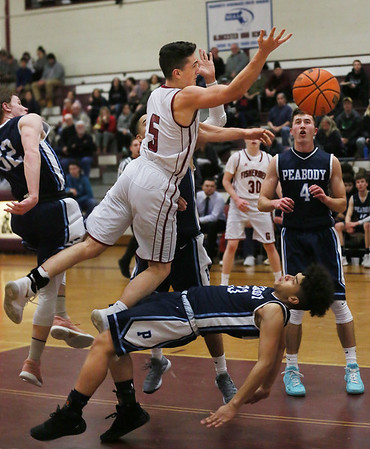 MIKE SPRINGER/Staff photo<br /> Gloucester's Brendan O'Brien goes up for a shot as Chris Canela of Peabody falls to the floor during varsity basketball action Tuesday in Gloucester.<br /> 2/13/2018