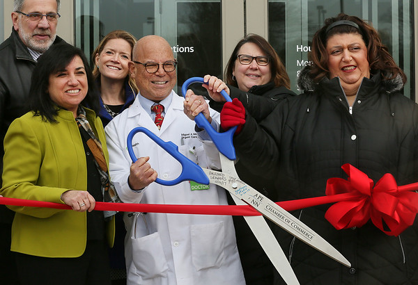 MIKE SPRINGER/Staff photo<br /> Dr. Miguel Martinez, medical director at the new Lahey Health Urgent Care, holds a giant pair of scissors during a ribbon-cutting ceremony Tuesday morning at Gloucester Crossing. From left are Barry Pett, director of community outreach for state Sen. Bruce Tarr; Terry Giove, executive director of Urgent Care; Christine Healey, director of community relations for Lahey Health; Martinez; state Rep. Ann-Margaret Ferrante; and Mayor Sefatia Romeo Theken.<br /> 02/06/2018