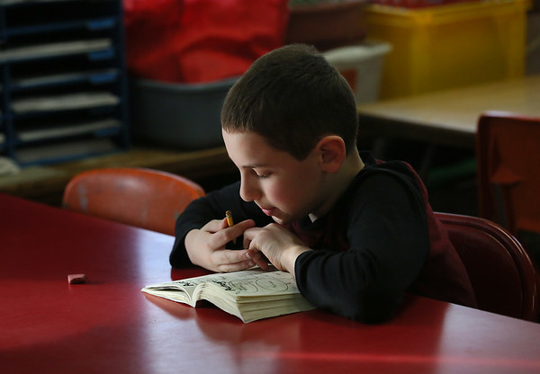 MIKE SPRINGER/Staff photo<br /> Third-grader Ben Secrest enjoys a book during the Cape Ann YMCA's after school program at Beeman Elementary School in Gloucester.<br /> 02/01/2018