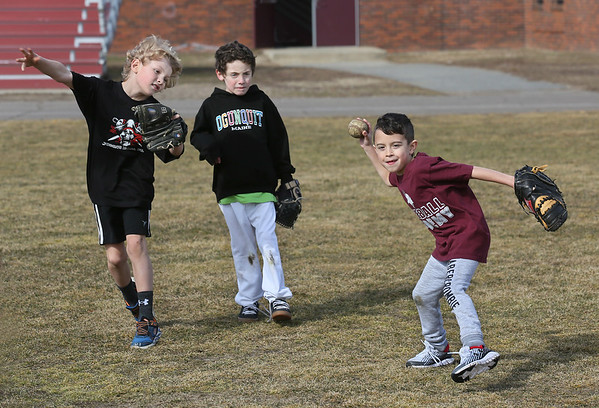 MIKE SPRINGER/Staff photo<br /> Seven-year-old Jordan Nicastro, right, prepares to throw the ball while taking part in a fielding exercise with Colson Gomez, left, and Jack Palmer, both 8, during the Rockport High School Vikings baseball skills clinic on Wednesday. Over 30 children, ages 7-12, are participating in the clinic.<br /> 2/21/2018