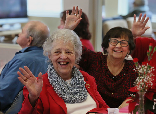 MIKE SPRINGER/Staff photo<br /> Marjorie Melanson, left, and Phyllis Camille wave to a video camera during the annual Valentine's Day luncheon Thursday at the Rose Baker Senior Center in Gloucester.<br /> 2/15/2018