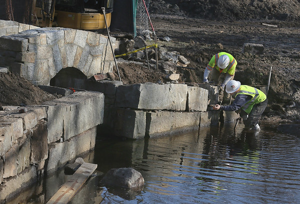 MIKE SPRINGER/Staff photo<br /> Zach Taylor, left, and Steven Chaves of the Peabody-based SumCo Eco-Contracting work together to move a granite block into place Wednesday while rebuilding the wall of the Frog Pond at Milbrook Meadow in Rockport. Since December, Sumco has removed about 300 tons of mud from the Frog Pond and about ten times that amount from the larger Mill Pond. Workers have also built a new stone staircase at the Frog Pond and are repairing walls around both ponds. The project is expected to be finished by late April.<br /> 2/14/2018
