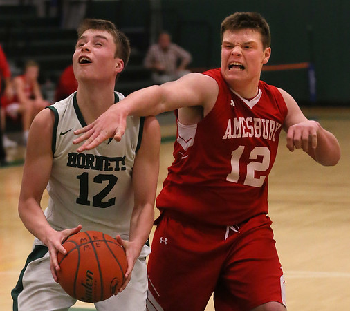 MIKE SPRINGER/Staff photo<br /> Harry Painter of Manchester Essex prepares to go up for a shot as Amesbury's Tom McAndrew tries to block the ball during varsity basketball action Friday in Manchester.<br /> 2/9/2018