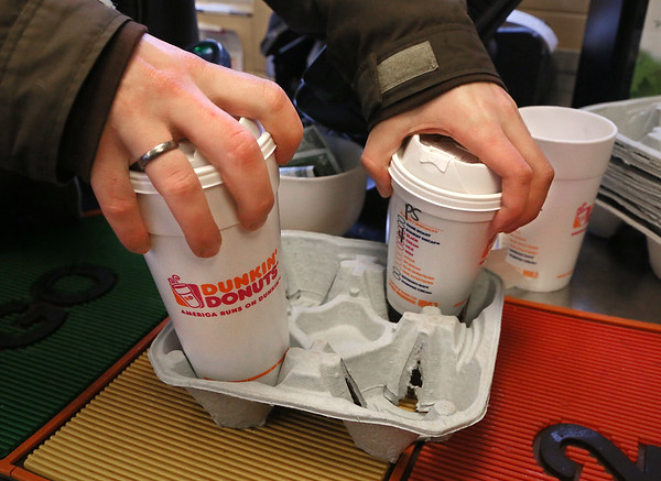 MIKE SPRINGER/Staff photo<br /> An employee puts two styrofoam cups in a tray Friday at the Dunkin' Donuts on Washington Street in Gloucester.<br /> 2/9/2018