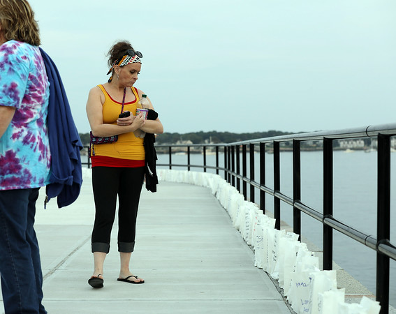 DAVID LE/Gloucester Times. Amanda Davidson, of Gloucester, walks along the Boulevard and reads names of those who had died from Opioid Abuse during a Vigil on Monday evening.