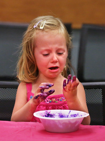 """MIKE SPRINGER/Staff photo<br /> Four-year-old Beatrice Hinderlie reacts to her dirty hands while making """"mermaid slime"""" during a children's event Monday at the Sawyer Free Library in Gloucester.<br /> 7/16/2018"""