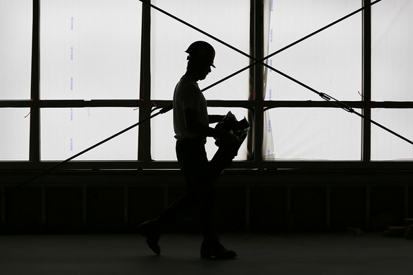 HADLEY GREEN/Staff photo<br /> A construction worker walks through the new GMGI headquarters building on the Gloucester waterfront.<br /> <br /> 07/05/2018