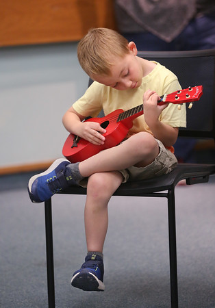 MIKE SPRINGER/Staff photo<br /> Seven-year-old Caine Comeau learns to play the ukulele during a workshop for children Thursday at the Sawyer Free Library in Gloucester.<br /> 7/19/2018