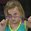 "MIKE SPRINGER/Staff photo<br /> Six-year-old Sydney Ryan paints a stick to turn it into a ""magic wand"" during a Harry Potter Week activity Monday at the Cape Ann YMCA's Camp Spindrift in Gloucester.<br /> 7/30/2018"