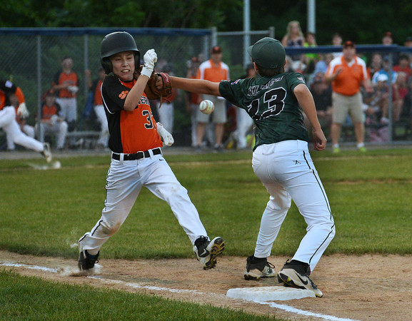 CARL RUSSO/staff photo. Beverly's Devin Koloski beats the throw to first base as Manchester Essex first baseman A J Altieri is unable to handle the throw. Beverly defeated Manchester Essex in Little League baseball action Thursday night.  7/5/2018