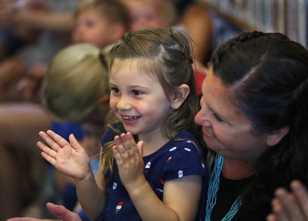 MIKE SPRINGER/staff photo<br /> Robin Kosma watches as her daughter Lucy, 3, claps along during a concert for children Wednesday by musician Charlie Hope at the Manchester Public Library.<br /> 7/11/2018