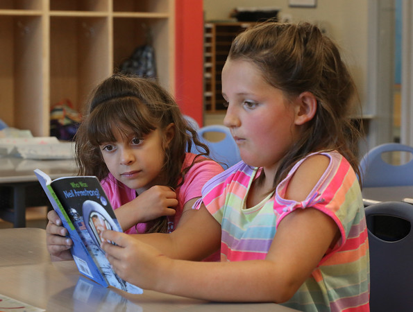 MIKE SPRINGER/Staff photo<br /> Second-graders Avery Benjamin, right, and Aliyah Capone read a book about Neil Armstrong during a Cape Ann YMCA summer reading class Friday at West Parish Elementary School in Gloucester.<br /> 7/20/2018