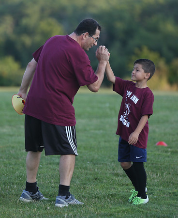 MIKE SPRINGER/Staff photo<br /> Coach Armando Marnoto gives a congratulatory high-five to Kyle Silva, 6, during the 7th-annual Cape Ann Soccer Camp Tuesday at Magnolia Woods in Gloucester. Eighty campers from four to 13 years of age have participated this summer.<br /> 7/31/2018