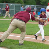AMANDA SABGA/Staff photo<br /> <br /> Gloucester's Lukas Albano (20) high fives a coach after making it to first during a game against Reading at Fernald Field in Wakefield. <br /> <br /> 7/14/18