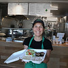 MIKE SPRINGER/Staff photo<br /> Mahroussie Jabba, owner of Markouk Bread at 338 Main Street in Gloucester, holds a lunch box containing one of her Lebanese specialties.<br /> 7/12/2018