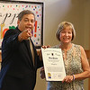 MIKE SPRINGER/Staff photo<br /> State Sen. Bruce Tarr points to a camera after presenting Judy Gallerie, assistant director of the Flint Public Library, with a proclamation in her honor from the Senate during Gallerie's retirement party Friday in Middleton. Gallerie is stepping down after 30 years of service at the library.<br /> 7/27/2018