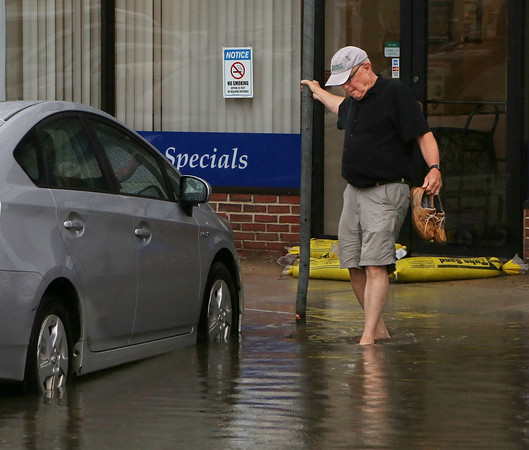 MIKE SPRINGER/Staff photo<br /> A man removes his shoes to step into the water to get to his car on Commercial Street following a torrential rain Tuesday afternoon in Gloucester.<br /> 7/17/2018