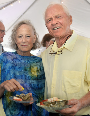 CARL RUSSO/staff photo. GLOUCESTER:  Liz Neumeier, president of the Gloucester Stage Co. Board of Directors and her guest Chuck Kelley of Gloucester enjoy shrimp and oysters. The Gloucester Stage Co. held their annual  2018 Gala on the Maritime Pier on Saturday (7/28) Dread Pirate (Artistic Director) Robert Walsh, enlisted an outstanding crew of swashbuckling performers to wow and immerse the audience with sword fights, sea songs, and a bit of rum. 7/28/2018