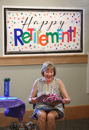 MIKE SPRINGER/Staff photo<br /> Judy Gallerie, assistant director of the Flint Public Library in Middleton, opens a present during her retirement party Friday at the library. Gallerie stepped down after 30 years of service to the library.<br /> 7/27/2018