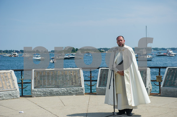 AMANDA SABGA/Staff photo<br /> <br /> Father Jim Achadinah, of Holy Family Church in Gloucester, says a prayer during the Blessing of the Fleet at the Fisherman's Memorial statue in Gloucester.<br /> <br /> <br /> 7/1/18