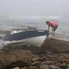 MIKE SPRINGER/Staff photo<br /> An investigator with the U.S. Coast Guard examines a recreational fishing boat after it ran aground in the fog Monday on Gloucester's Back Shore. The lone occupant, a Gloucester man, ran the boat aground intentionally after it struck a rock and began taking on water. He was not hurt.<br /> 7/16/2018