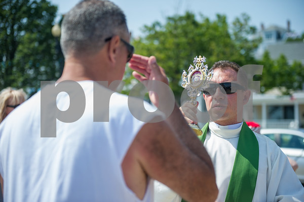 AMANDA SABGA/Staff photo<br /> <br /> Father Robert Bedzinski, of the John Paul II Shrine of Divine Mercy in Salem, blesses people with a relic of Pope John Paul II during the Blessing of the Fleet at the Fisherman's Memorial statue in Gloucester.<br /> <br /> <br /> 7/1/18