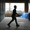 HADLEY GREEN/Staff photo<br /> A construction worker walks through the bottom floor of the new GMGI headquarters building on the Gloucester waterfront.<br /> <br /> 07/05/2018