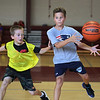 MIKE SPRINGER/Staff photo<br /> Ten-year-old Sean Broe, left, of Rockport guards Sam Sanfilippo, also 10, of Gloucester as he passes the ball off to the side without looking during a scrimmage Tuesday at the Cape Ann Basketball Camp at Rockport High School.<br /> 7/17/2018