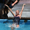 MIKE SPRINGER/Staff photo<br /> Twelve-year-old Madison Moseley of Rockport splashes into the pool after sliding down a ramp of solid ice Thursday at Cape Ann YMCA's Camp Spindrift in Gloucester. The slide was made out of ice blocks provided by Cape Pond Ice.<br /> 7/12/2018