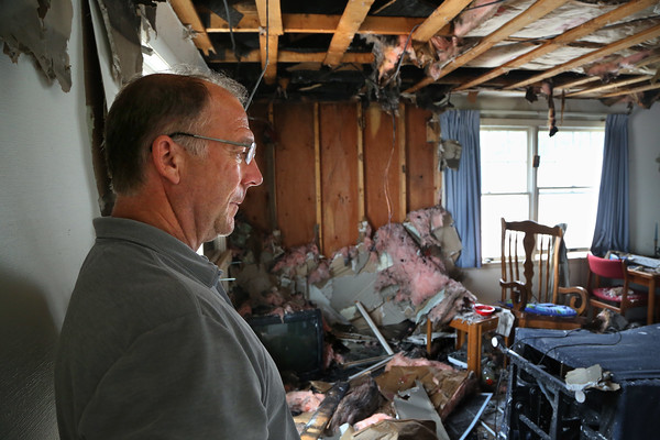 """MIKE SPRINGER/Staff photo<br /> Owner Alan Battistelli looks Monday at a fire-damaged room on the second floor of the Cape Hedge Inn in Rockport. The inn was badly damaged Sunday in an early morning fire. Battistelli expressed relief that all of his tenants escaped the fire. """"Buildings can be replaced,"""" he said, """" but people can't.""""<br /> 7/30/2018"""