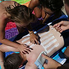 HADLEY GREEN/Staff photo<br /> From left, Grace Cunningham of Marblehead, Talia Monkiewicz of Georgetown, and Amanda Lee of Georgetown paint an American flag using sunscreen on the back of James McGrath, of Haverhill, at Half Moon Beach in Stage Fort Park in Gloucester. <br /> <br /> 07/05/2018