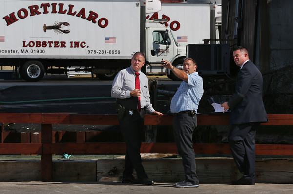 MIKE SPRINGER/Staff photo<br /> Gloucester police detective Thomas Quinn, center, briefs a pair of state investigators Tuesday after the body of a man was discovered and removed from beneath a pier at Harbor Cove in Gloucester.<br /> 7/10/2018