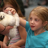 MIKE SPRINGER/Staff photo<br /> Five-year-old Nevaeh Steadman reaches out to pet a Chinese Silkie during a presentation of rare chickens from around the world Friday at the Sawyer Free Library in Gloucester. More than 50 children attended the event.<br /> 7/20/2018