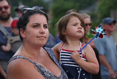 MIKE SPRINGER/Staff photo Mercedes Lane holds her friend's daughter Violeta Aprans, 3, Tuesday as they watch the 75th annual Fishtown Horribles Parade in Gloucester. 7/3/2018