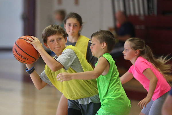 MIKE SPRINGER/Staff photo<br /> Ten-year-old Logan Frogod of Rockport looks for someone to pass to during a scrimmage Tuesday at the Cape Ann Basketball Camp at Rockport High School. Around him are, from background left, Ally Piscitello, 12, of Rockport, Cam Olsen, 10, of Gloucester and Addie Gardner, 11, of Rockport.<br /> 7/17/2018