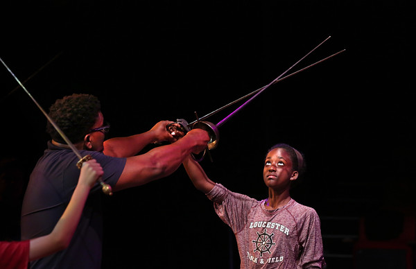 """MIKE SPRINGER/Staff photo<br /> Devin Christor, a stage management apprentice with training in stage combat, teaches 12-year-old Bezzie Strong of Gloucester the art of dramatic sword fighting on Friday during the Gloucester Stage Company's Youth Acting Workshops. The current Gloucester Stage production, """"Cyrano,"""" features sword fighting.<br /> 7/20/2018"""