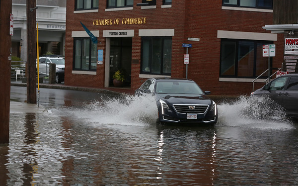 MIKE SPRINGER/Staff photo<br /> A car moves through a flooded area of Commercial Street following a torrential rain Tuesday afternoon in Gloucester.<br /> 7/17/2018