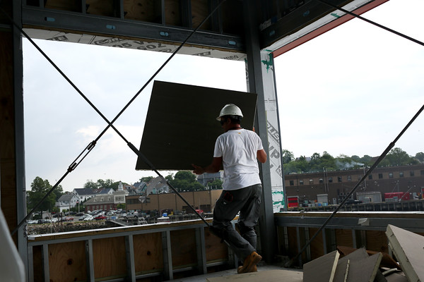 HADLEY GREEN/Staff photo<br /> A construction worker moves materials while working on the new GMGI headquarters building on the Gloucester waterfront. <br /> <br /> 07/05/2018