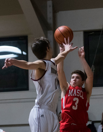 SAM GORESH/Staff photo. Masconomet's Patrick Osgood shoots the ball as Rockport's Jacob Knowlton attempts to block him on defense in their game at Rockport High School. 1/24/17