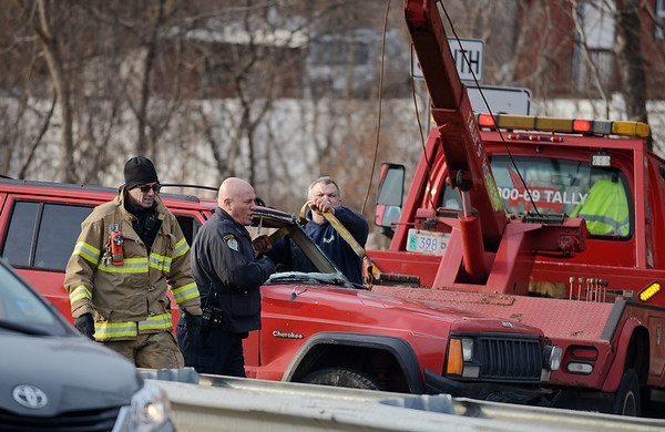 RYAN HUTTON/ Staff photo<br /> Emergency personnel and a wrecking crew turn a Jeep Grand Cherokee right-side-up after it rolled over at Grant Circle on Tuesday afternoon.