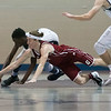 SAM GORESH/Staff photo. Peabody sophomore Chibuikem Onwuogo and Gloucester senior Nate Young dive for a loose ball in their game at Peabody High School. Peabody won the game 67-42. 1/20/17
