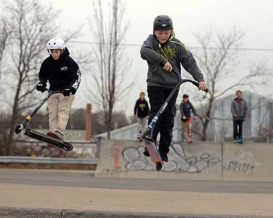 RYAN HUTTON/ Staff photo<br /> Greg Auditore, 13, right, and Russell Kenyon, 12, left, both go in for a landing on a ramp at the skate park at O'Maley Innovation Middle School.