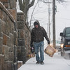 SAM GORESH/Staff photo. Gloucester resident Mike DeMetri walks home from the grocery store as the snow begins t pick up. 1/7/17