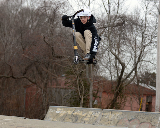 RYAN HUTTON/ Staff photo<br /> Russell Kenyon, 12, grabs the base of his scooter while getting some air at the skate park at O'Maley Innovation Middle School.