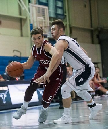 SAM GORESH/Staff photo. Gloucester sophomore Oliver Benjamin races down the court with the ball as Peabody senior Jake Doherty attempts to stop him on defense in their game at Peabody High School. Peabody won the game 67-42. 1/20/17