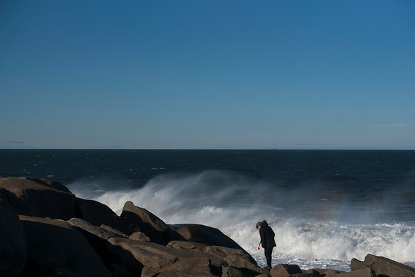 SAM GORESH/Staff photo. Eric Bishop walks with his dog Webby (not pictured) on the rocks at Halibut Point State Park. 1/25/17