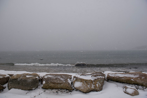 SAM GORESH/Staff photo. A wave crashes on the shore of the beach at Stage Fort Park during the snow storm. 1/7/17