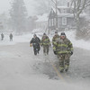 MIKE SPRINGER/Staff photo<br /> Firefighters and a police officer walk across a flooded area of East Main Street at high tide during the snowstorm Thursday in Gloucester.<br /> 01/04/2018