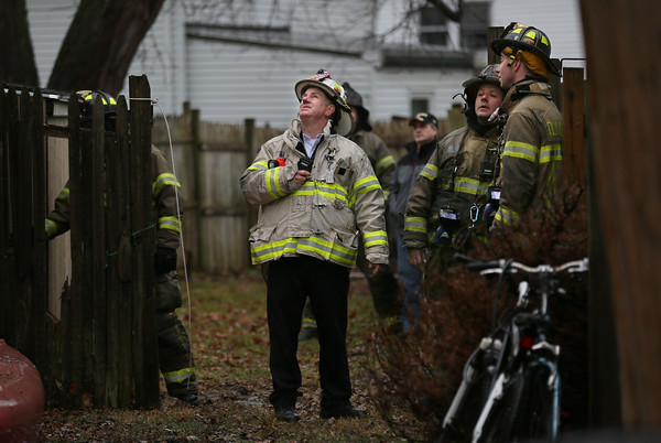 MIKE SPRINGER/Staff photo<br /> Deputy Fire Chief Stephen Aiello looks up at a badly damaged house at 33 Grove Street in Gloucester after firefighters put out a fire Tuesday morning.<br /> 01/23/2018