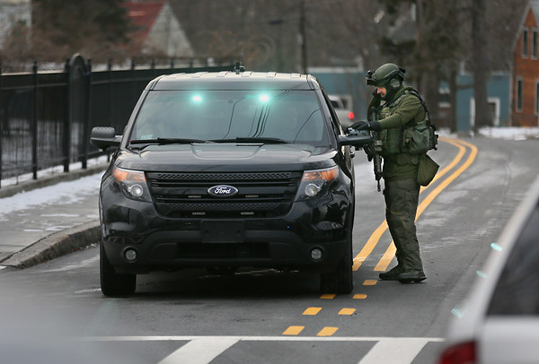 MIKE SPRINGER/Staff photo   <br /> A SWAT team member from the Northeastern Massachusetts Law Enforcement Council (NEMLEC) talks with another law enforcement officer on Washington Street Tuesday afternoon during a standoff nearby on Munsey Lane in Lanesville.<br /> 01/16/2018